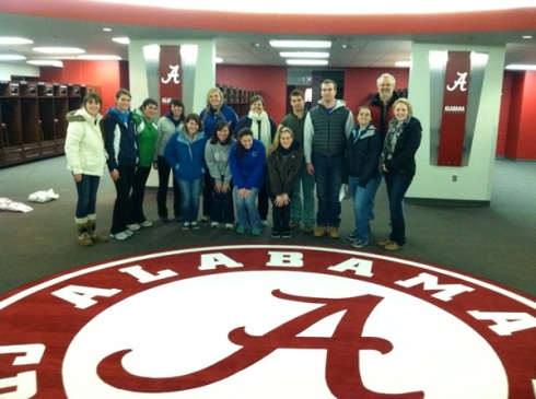 Assumption's 2013 team in Bama locker room, next to sacred seal on which only Nick Saban may trod.