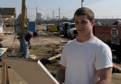 Nick smiles at autographs on board at construction site.