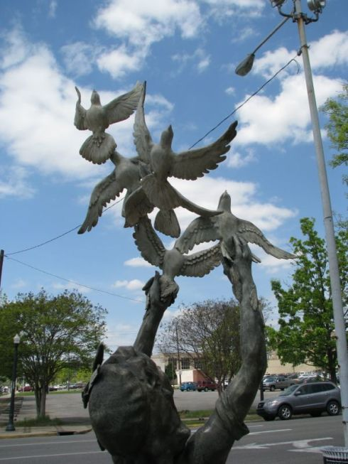 "One of the ""four spirits"" releases doves into air across intersection from 16th Street Baptist."
