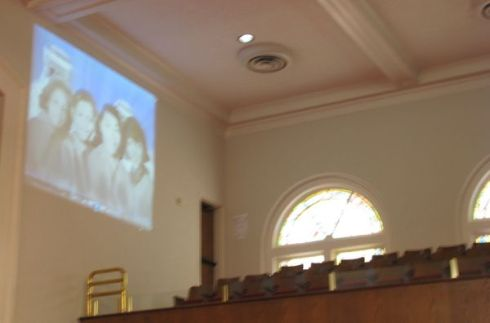 The four girls projected on wall of their church, part of video visitors see.
